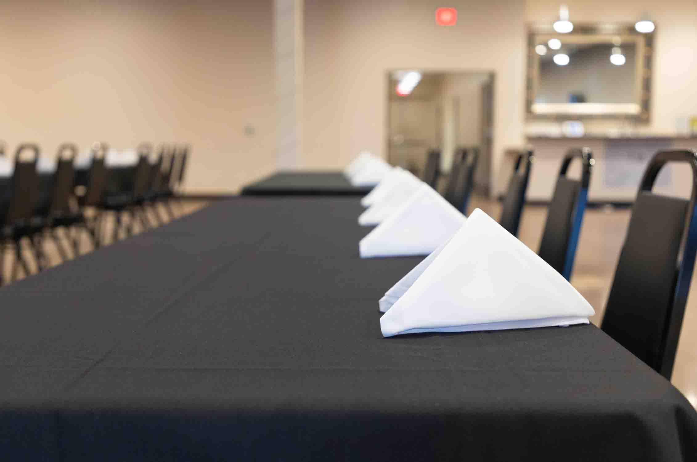 tables with napkins set up at corporate event