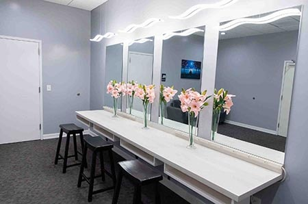 bridal room at lavela with gray walls, mirrors, black barstools and pink flowers in vases