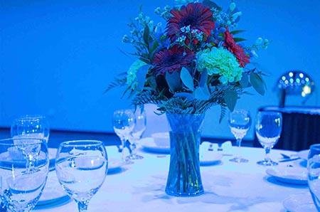 dinner table setup with floral centerpiece and dishware